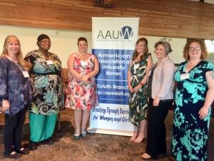 Women standing by AAUW banner